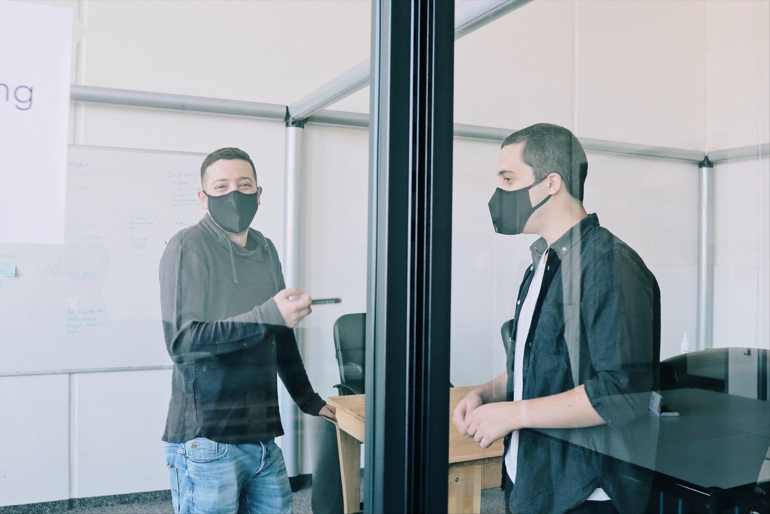 Alex (links) und Hugo (rechts) freuen sich, wieder im Nomoko-Büro zu sein, nachdem sie so lange von zu Hause aus gearbeitet haben